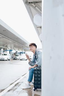 Jonge aziatische passagier wachten op taxi op de luchthaven