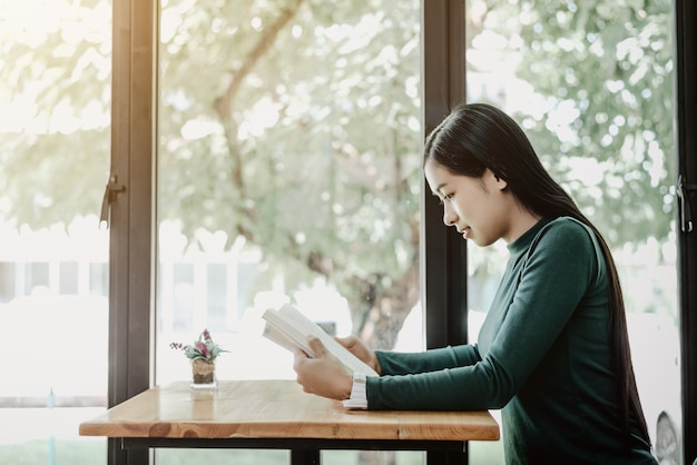 Jonge aziatische positieve student readin interessant boekzitting dichtbij glazenvensters.