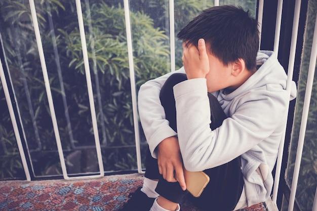 Jonge aziatische preteen tienerjongen knuffelen zijn knie en bedekken zijn gezicht en houden een telefoon, cyberpesten in kind, depressieve kind geestelijke gezondheid