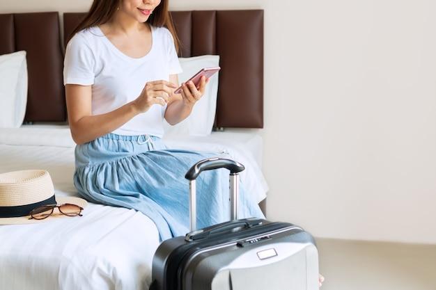 Jonge aziatische reiziger ontspannen en met behulp van smartphone in hotelkamer