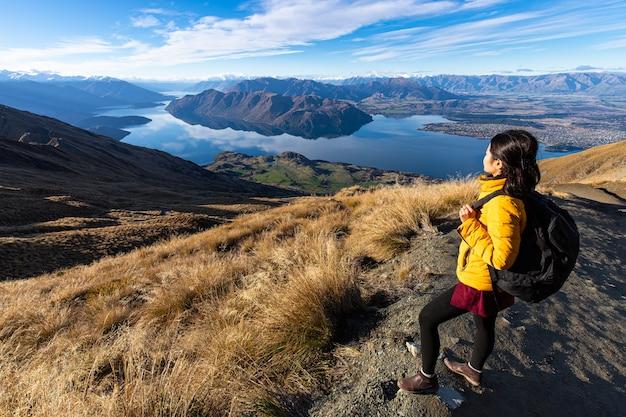 Jonge aziatische reizigersrugzak die op roys-piekspoor, wanaka, zuidereiland, nieuw zeeland wandelen