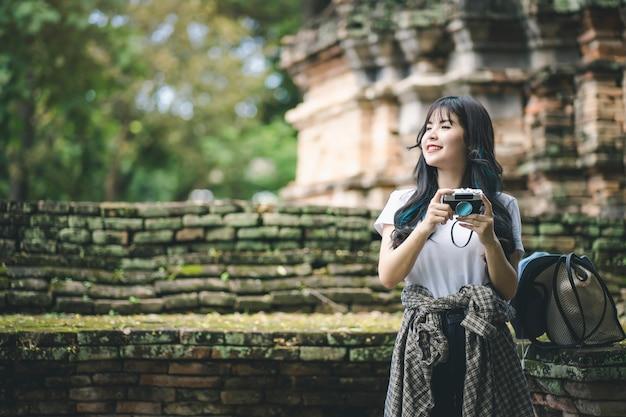 Jonge aziatische reizigersvrouw die foto nemen terwijl het reizen rond thaise oude tempel