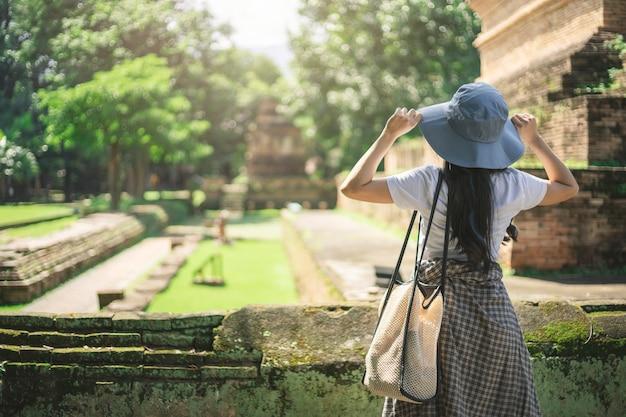 Jonge aziatische reizigersvrouw die terwijl het reizen rond thaise oude tempel glimlachen