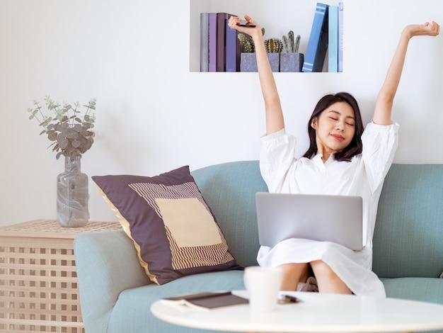Jonge aziatische schoonheid die haar armen uitrekt na het gebruik van een laptop.
