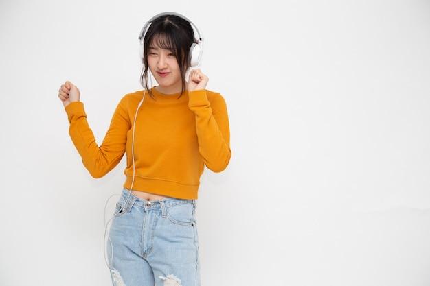 Jonge aziatische schoonheid vrouw luisteren muziek met koptelefoon op witte muur