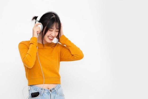 Jonge aziatische schoonheidsvrouw het luisteren muziek met hoofdtelefoons
