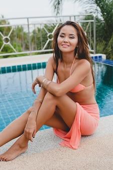Jonge aziatische sexy mooie vrouw in roze bikini, zittend aan het zwembad, slank, gebruinde huid, glamour modeaccessoires, armbanden, ontspannen, glimlachen, sensueel, zomervakantie