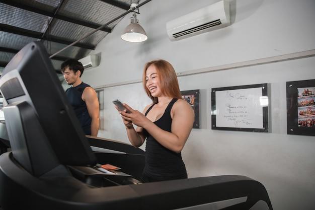 Jonge aziatische spiervrouwen lopen op smartphone van de tredmolenholding
