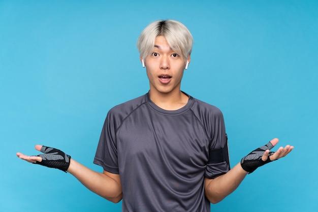 Jonge aziatische sportmens met geschokte gelaatsuitdrukking