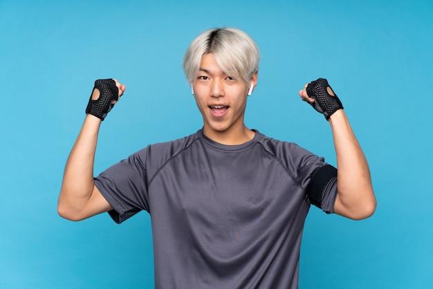 Jonge aziatische sportmens over geïsoleerd blauw die een overwinning vieren