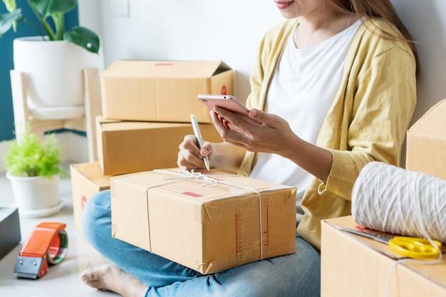 Jonge aziatische start kleine ondernemer schrijven adres op kartonnen doos op de werkplek. online verkoop, e-commerce, verzendconcept