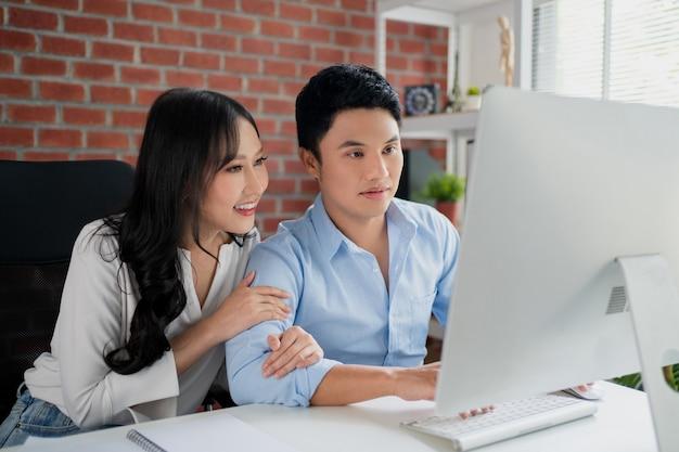 Jonge aziatische stellen genieten graag van hun weekend. de jonge vrouw glimlachte en omhelsde haar man die naar het laptopscherm keek tijdens het winkelen op een online website.