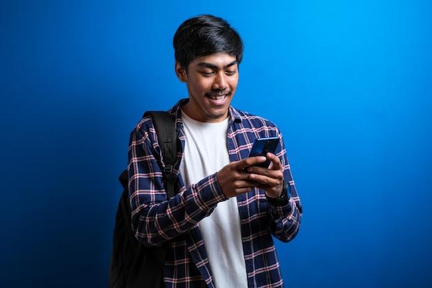 Jonge aziatische student glimlach en gebruik telefoon geïsoleerd op blauwe achtergrond. de man ziet er gelukkig uit als hij met zijn vriend praat