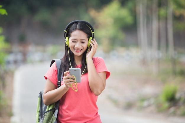 Jonge aziatische student in haar buitenactiviteit, luisteren naar de mu
