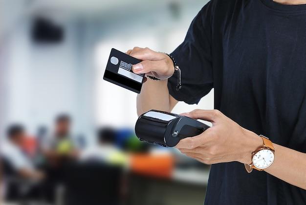 Jonge aziatische student met een electronic data capture (edc)-machine en klaar om creditcard of bankpas te vegen om te betalen over een prachtige wazige achtergrond. betalingsconcept