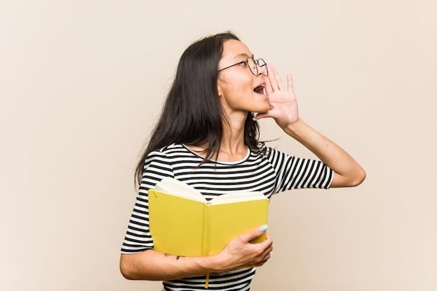 Jonge aziatische studente die een boek houden schreeuwend en palm houden dichtbij geopende mond.