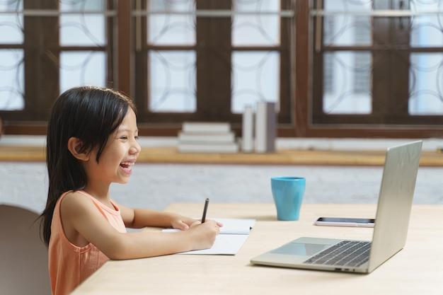 Jonge aziatische studente die studeert terwijl ze de computer gebruikt voor videogesprekken thuis. online e-learning onderwijs, terug naar school concept