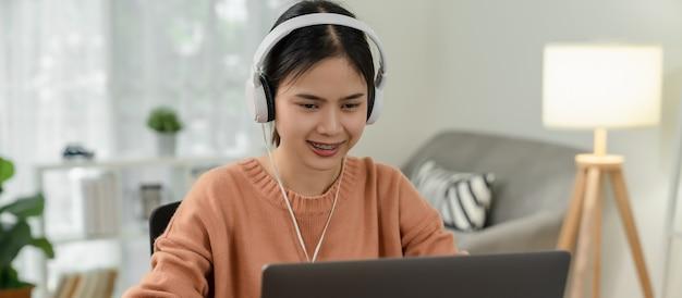 Jonge aziatische studente dragen witte hoofdtelefoons