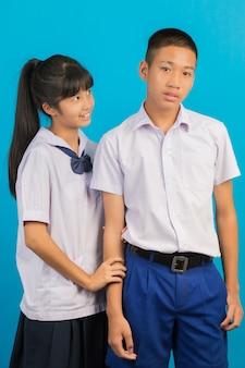 Jonge aziatische studenten en aziatische mannelijke studenten staan samen op een blauw.