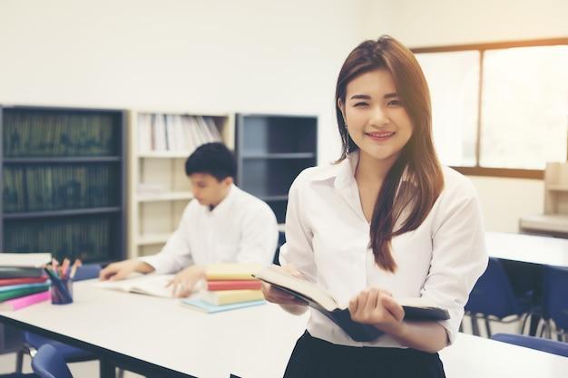 Jonge aziatische studenten in de bibliotheek lezen van een boek. onderwijsconcept.