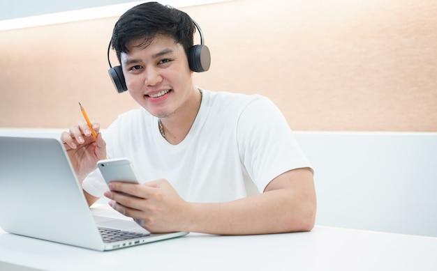 Jonge aziatische studentenmens die hoofdtelefoon draagt die online cursus leert