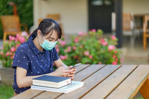 Jonge aziatische studentenvrouw die medisch masker dragen en smartphone houden, het scherm bekijken, app gebruiken of overseinen terwijl het zitten bij tuinbank met boek. nieuw normaal concept na covid-19