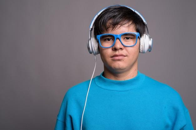 Jonge aziatische tiener die aan muziek tegen grijze chtergro luistert