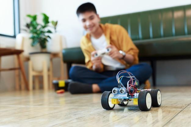 Jonge aziatische tiener die energie en signaalkabel aansluit op sensorchip van speelgoedautowerkplaats.
