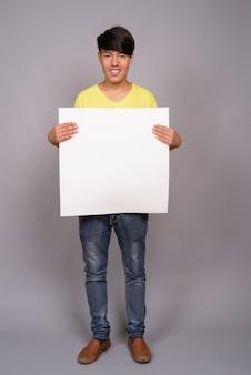 Jonge aziatische tiener die geel overhemd draagt tegen grijze muur