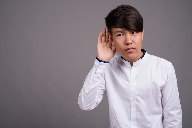 Jonge aziatische tiener die slimme vrijetijdskleding draagt tegen grijze muur