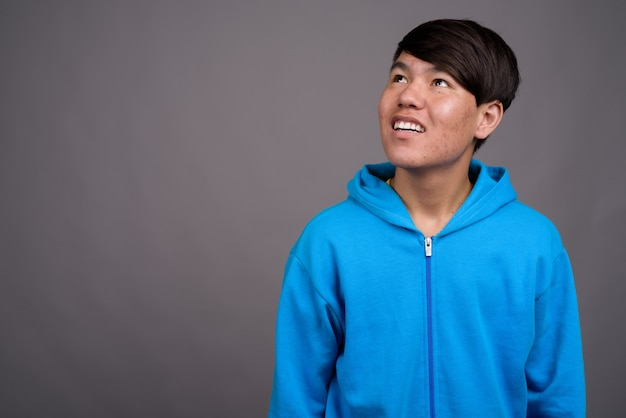 Jonge aziatische tiener draagt blauwe jas tegen grijze muur