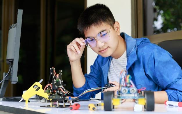 Jonge aziatische tiener geniet met speelgoedautoworkshop.