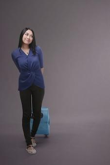 Jonge aziatische toerist die blauwe koffer draagt