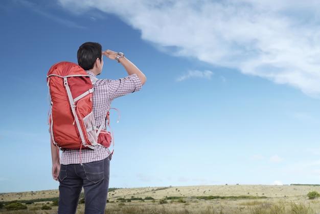 Jonge aziatische toeristenmens die met rugzak blauwe hemel bekijken