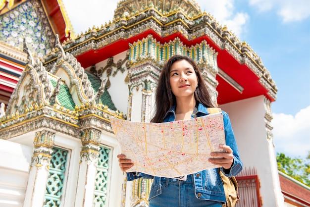 Jonge aziatische toeristenvrouw die backpacker solo in oude thaise tempel reizen tijdens de zomervakanties in bangkok thailand