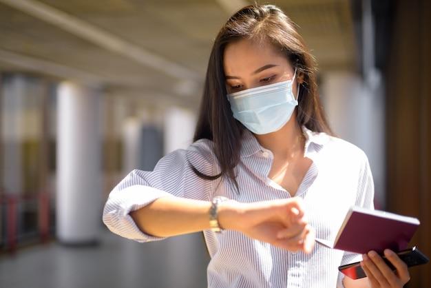 Jonge aziatische toeristenvrouw die met masker de tijd controleert terwijl zij paspoort op de luchthaven houdt