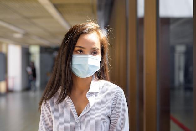 Jonge aziatische toeristenvrouw die met masker denkt voor bescherming tegen de uitbraak van het coronavirus op de luchthaven