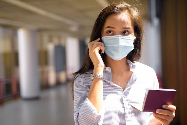 Jonge aziatische toeristenvrouw met masker die aan de telefoon spreken terwijl zij paspoort op de luchthaven houdt