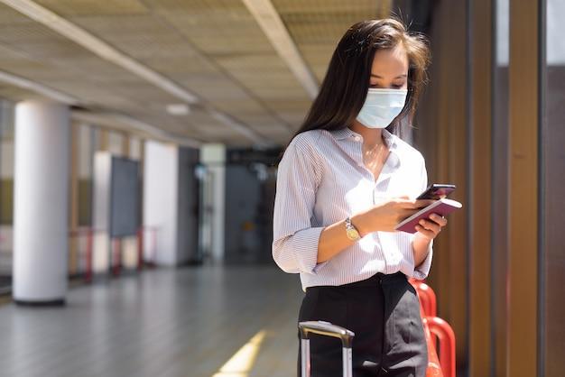Jonge aziatische toeristenvrouw met masker die telefoon met behulp van en paspoort op de luchthaven houden