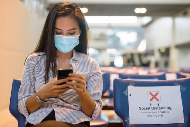 Jonge aziatische toeristenvrouw met masker die telefoon met behulp van zittend met afstand op de luchthaven