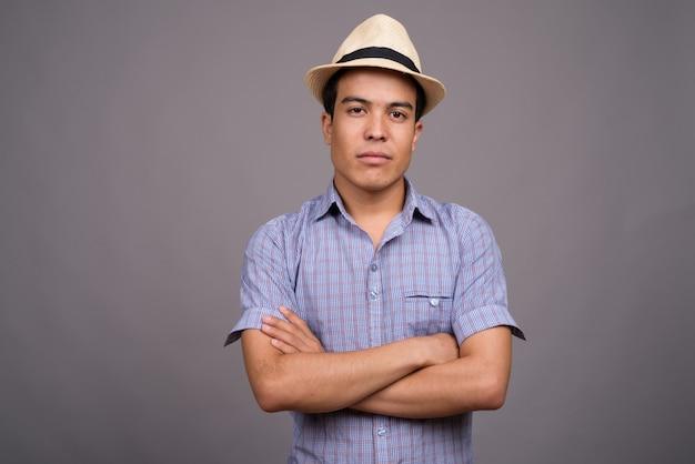 Jonge aziatische toeristische man met hoed klaar voor vakantie tegen grijze muur