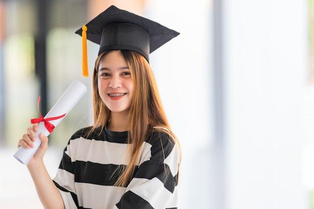 Jonge aziatische universitaire afgestudeerden in afstudeerjurk en baret hebben een diploma