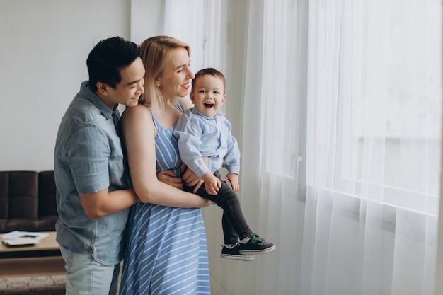 Jonge aziatische vader en blanke blonde moeder houdt zoon in haar armen in lichte kamer. multicultureel trendy concept