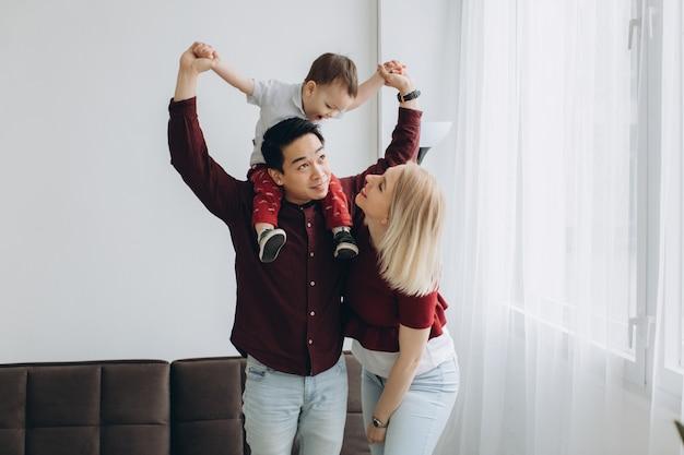 Jonge aziatische vader en europese blonde moeder houden zoon in haar armen in lichte kamer. multicultureel trendy concept