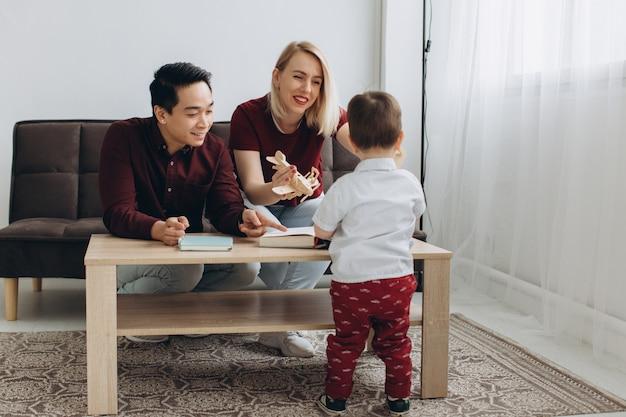 Jonge aziatische vader en europese blonde moeder spelen zitten met haar zoon in lichte kamer