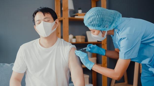Jonge aziatische verpleegster die covid-19 of griep-antivirusvaccin geeft aan mannelijke patiënt, draagt gezichtsmasker ter bescherming tegen virussen