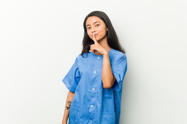 Jonge aziatische verpleegstersvrouw die een geheim houdt of om stilte vraagt.