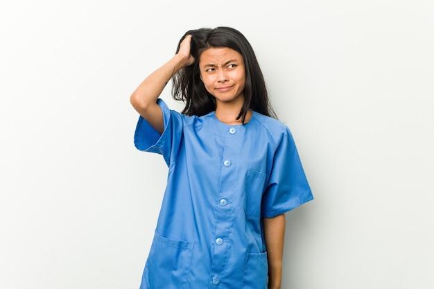 Jonge aziatische verpleegstersvrouw die geschokt is, herinnert zij zich belangrijke vergadering.