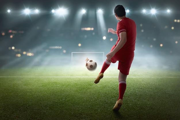 Jonge aziatische voetballer die de bal schiet