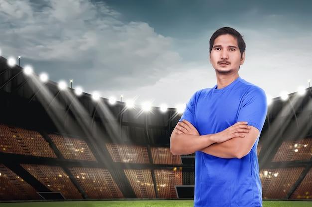 Jonge aziatische voetballer die zich met gekruiste wapens bevindt
